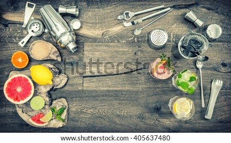 Fruit drinks with ice. Cocktail making bar tools, shaker, glasses. Flat lay. Vintage style toned picture - stock photo