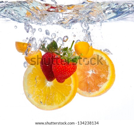 Fruit falling into water clear ripple fresh red orange - stock photo