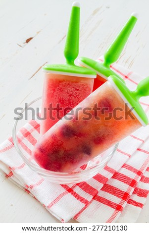 Fruit ice pops (watermelon, berry, orange) in glass bowl, plaid napkin, white wood background - stock photo