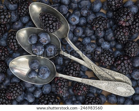 Fruit in rustic setting with vintage spoons on table - stock photo