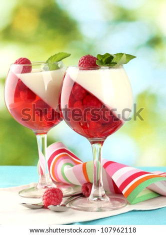 fruit jelly in glasses, berries and mint on table on green background - stock photo