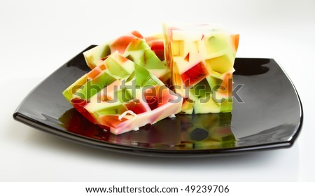 Fruit jelly on black plate on white background - stock photo