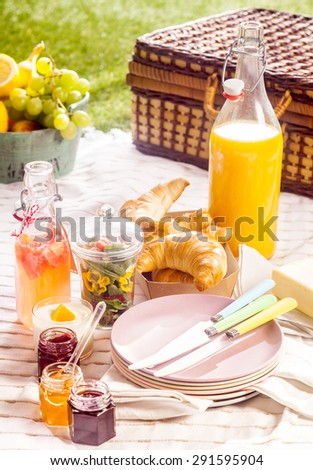Fruit juice, croissants and fresh fruit for a summer picnic laid out on a blanket on a green lawn with a rustic wicker hamper - stock photo