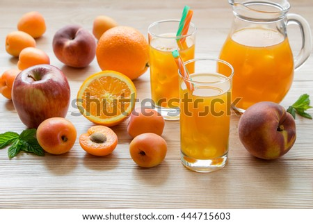 Fruit juice in glasses with ice near the jar of juice and scattered apricots, peaches, apple, orange on a light wooden background. Apricot peach apple orange juice with ice. Horizontal.