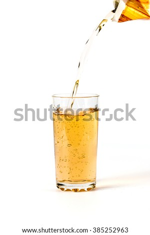 Fruit juice is poured into a beaker on a white background