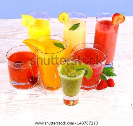 Fruit juices, kiwi, raspberries, cherry, orange, strawberry, pineapple, top view - stock photo