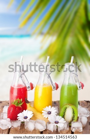 fruit juices with fresh fruits and ice on wooden table on natural background, beach at seychelles