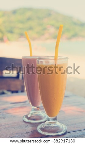 Fruit mango shakes on the background of a tropical beach. Beach cafe - stock photo