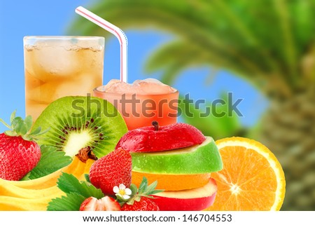 Fruit mix and cocktail on a beach background