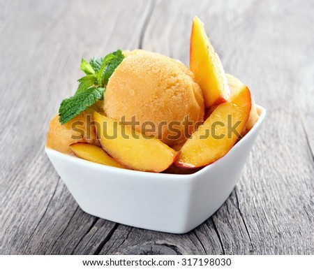 Fruit peach sorbet with mint in a bowl on wooden table - stock photo