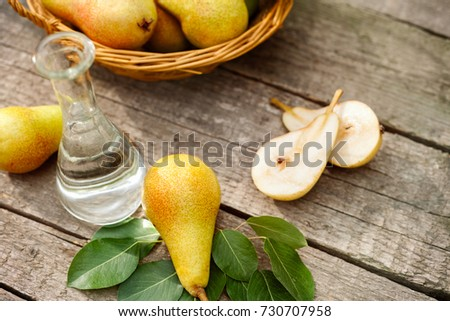 Fruit pears on the table with glass bottle of pear brandy