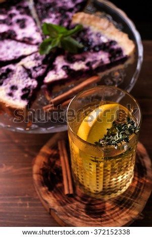 Fruit pie and hot tea with lemon and herbs - stock photo