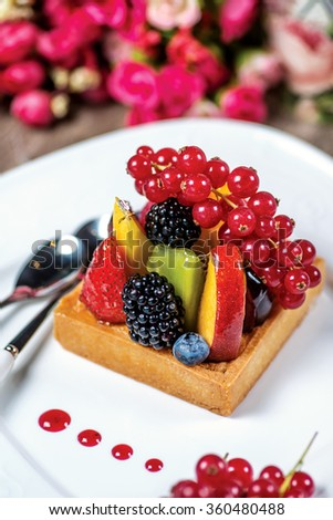 Fruit pie or cake with apple, blackberry, strawberry and mango and kiwi. A delicious fruit tart. - stock photo