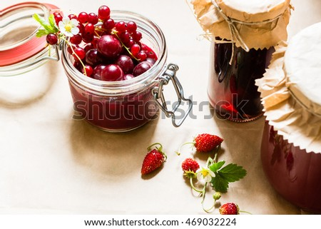 Fruit preserves and raw strawberries , cherries and red currants berries on a kitchen table, organic meal and dessert concept
