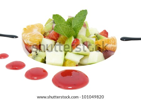 fruit salad decorated with mint on a white plate