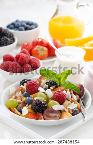 fruit salad in a bowl and various yoghurt, vertical, close-up
