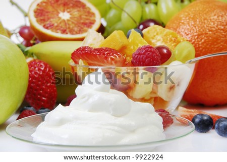 fruit salad in a bowl, with cream and arranged in front of fresh fruits