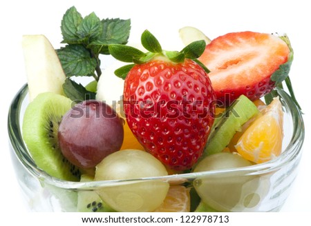 Fruit salad in a glass bowl on white background