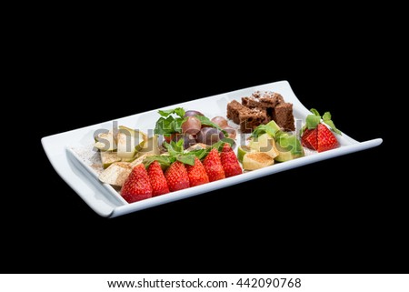 fruit salad in a plate with cookies on a black background