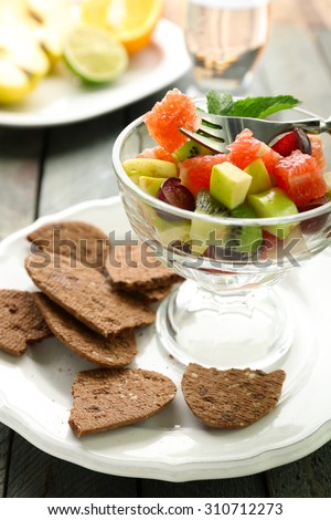 Fruit salad in glass bowl, on wooden background