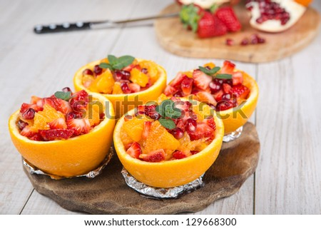 Fruit salad in hollowed-out orange. On wooden table. - stock photo