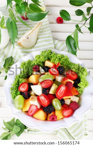 Fruit salad in plate on wooden table