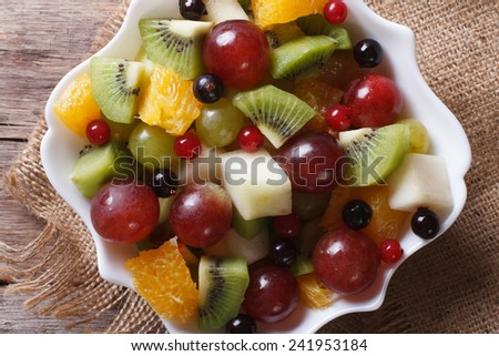 Fruit salad in white plate on the table close-up. horizontal view from above, rustic style  - stock photo