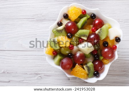 Fruit salad of oranges, grapes. pears, kiwi in white plate close up. horizontal view from above  - stock photo