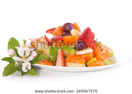 Fruit salad on a plate, with apple blossoms next to it - stock photo
