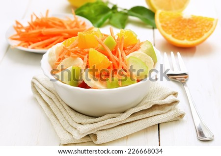 Fruit salad with carrots, apples, bananas and orange slices in bowl on white wooden table - stock photo