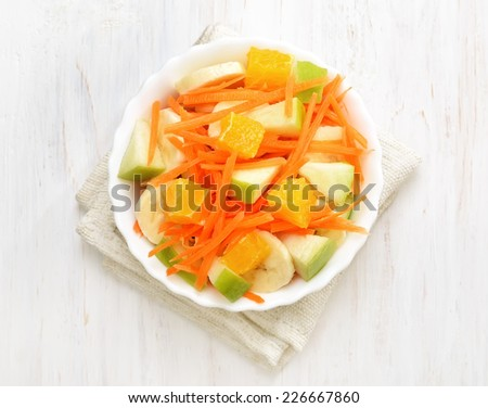 Fruit salad with carrots, apples, bananas and orange slices in bowl on white wooden table, top view - stock photo