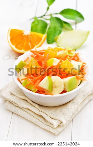 Fruit salad with carrots, apples, bananas and orange slices in the bowl on white wooden table - stock photo