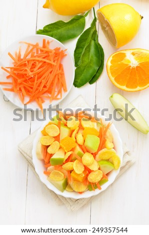 Fruit salad with cornflakes on white wooden table, top view - stock photo