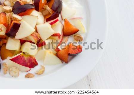 fruit salad with fresh plums, apples and hazelnuts/fruit salad/food - stock photo