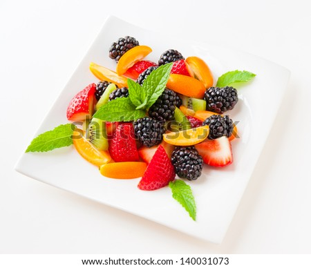 Fruit salad with fresh strawberries, blackberries,  kiwis and  kumquats on a plate on light background. Healthy eating, berry dessert. selective focus.