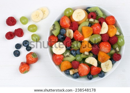Fruit salad with fruits like strawberries, blueberries, kiwi and apricots from above - stock photo