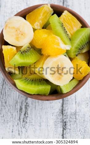Fruit salad with kiwi, banana and orange in the bowl on the wooden board