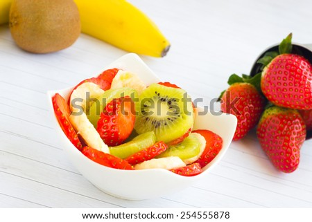 Fruit salad with kiwi, banana and strawberry on a white table. Healthy snack choice. - stock photo