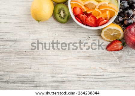 Fruit salad with ripe fruits on wooden table - stock photo