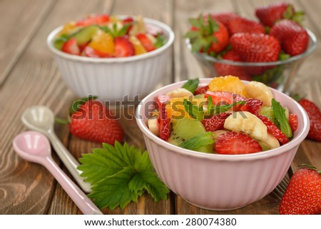 Fruit salad with strawberries on a  brown background - stock photo