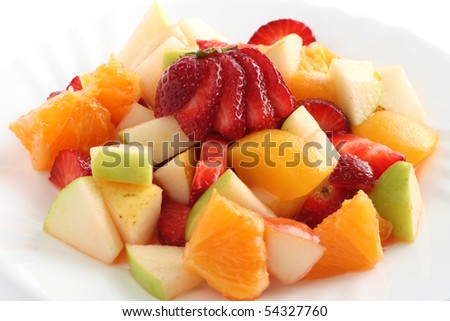 fruit salad with strawberry, orange, apple in white dish