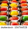Fruit shaped candies in macro image of marzipan sweets in paper wrappings - stock photo