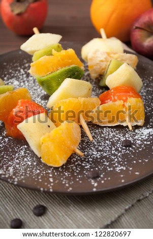 Fruit skewers with apple, persimmon, kiwi and citrus orange