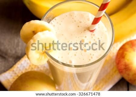 Fruit smoothie (banana, apple, peach) on wooden background - stock photo