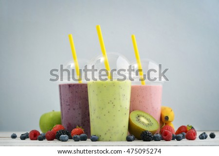 Fruit smoothies in plastic cups with blueberry, strawberry, kiwi, blackberry, raspberry and banana on blue background. Take away drinks concept.