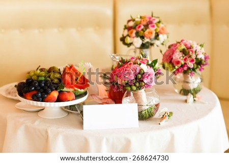 Fruit stil vase with flowers white tablecloth - stock photo