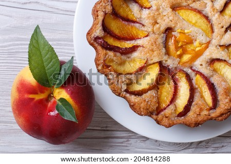 fruit tart and fresh peach closeup on a wooden table top view horizontal