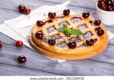 Fruit tart with cherry filling and fresh sweet cherries and mint, selective focus - stock photo