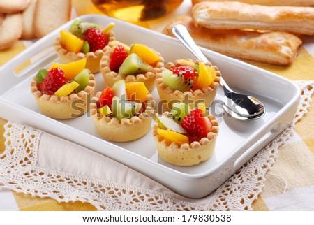 Fruit tartlets on a white tray. - stock photo