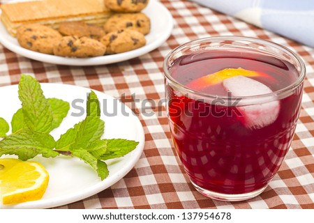 Fruit tea breakfast with cookies, lemon and peppermint.
